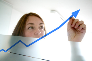 Business woman draws an arrow on a graph